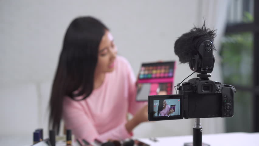 Beauty blogger present beauty cosmetics while sitting in front camera for recording video. Beautiful woman use brush while review make up tutorial broadcast live video to social network by internet.