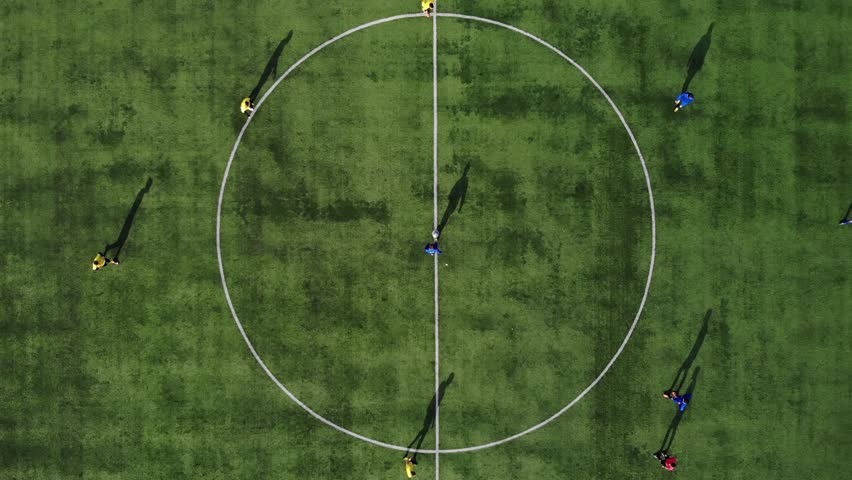 Aerial football match start. Beginning of game. Aerial shot Two teams playing ball in football outdoors, top view. Football game outdoors, green field with markings, players running around with a ball