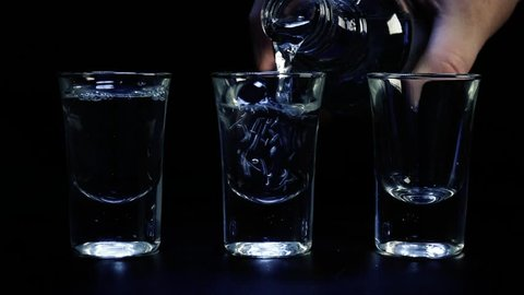 Pouring up three shots of vodka in glass against black background