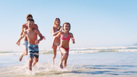 Parents and Children In Swimsuits Running Out Of Sea On Summer Vacation