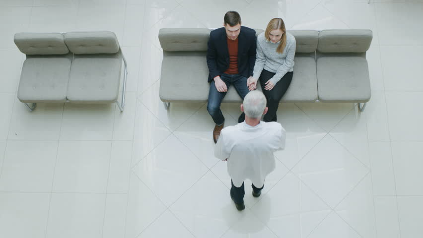 High Angle Shot in the Hospital, Young Couple Sitting in the Lobby Waiting for Test Results Receive Good News from their Doctor. Happy Moment in the Life of Young People. Shot on RED EPIC-W 8K Camera.