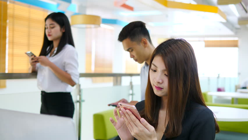 Advertising, Education, Business, Technology, Communication concept - Addiction to smartphones. Beautiful young asian woman using smartphone in office with friend and Smiling, Looking at camera. | Shutterstock HD Video #1011665144