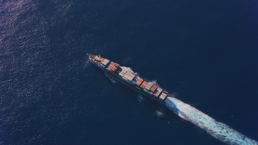 Oahu, Hawaii circa-2018. Overhead aerial view of container ship in ocean. Shot with Cineflex and RED Epic-W Helium.