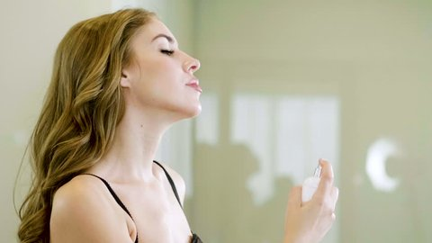 Beautiful blonde woman spraying perfume on her neck.
