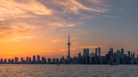 The historic Toronto city skyline office buildings and condos in the midst of this beautiful sunset with orange, yellow, red, and purple clouds along the horizon.