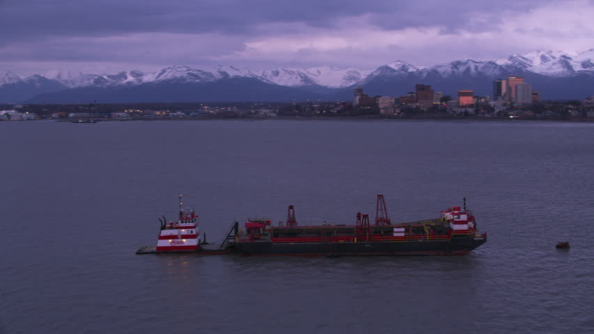 Anchorage, Alaska circa-2018. Aerial view of barge and tug boat in Anchorage, Alaska. Shot from helicopter with Cineflex gimbal and RED Epic-W camera.