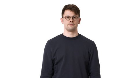 Concentrated man in black sweatshirt and glasses wishing holding hands together for pray with closed eyes, isolated over white background. Concept of emotions