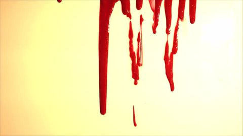 Blood splatter. Blood dripping down over light background. Red liquid.