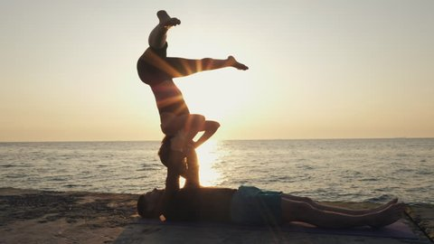 Silhouettes of fit young couple doing acro-yoga at sea beach. Man lying on concrete plates and balancing woman in his feet. Beautiful couple practicing yoga together, slow motion