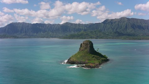 Oahu, Hawaii circa-2018. Aerial view of Mokolii Islet also known as Chinaman's Hat. Shot with Cineflex and RED Epic-W Helium.