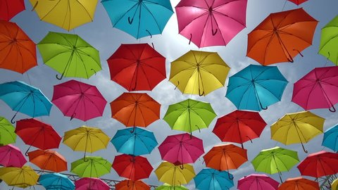 Tilt shot of the colorful umbrellas hanging in the sky