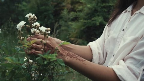 Close up shot of woman touching and enjoying wild flowers in a forest. Woman with exotic white flowers outdoor in nature. Henna art.