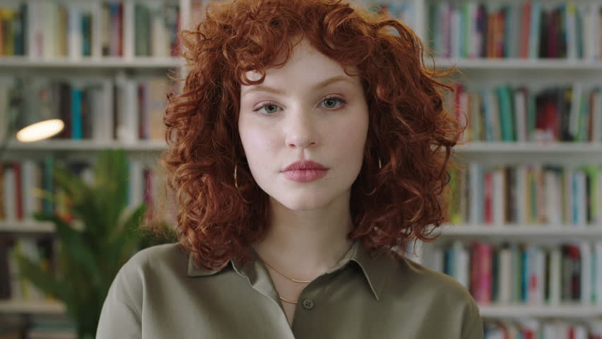 portrait of seductive young librarian woman standing in library attractive student smiling close up red head