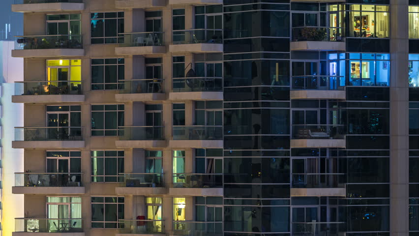 Glowing windows of skyscrapers at night timelapse. View of modern residential high-rise buildings in Dubai marina. People moving inside. Aerial top view.   Shutterstock HD Video #1011785354