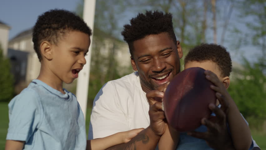 Ottawa, Canada - May 2018 - An african american father plays with his kids in a soccer pitch beside an urban housing development setting a positive example for the next generation of children | Shutterstock HD Video #1011786824