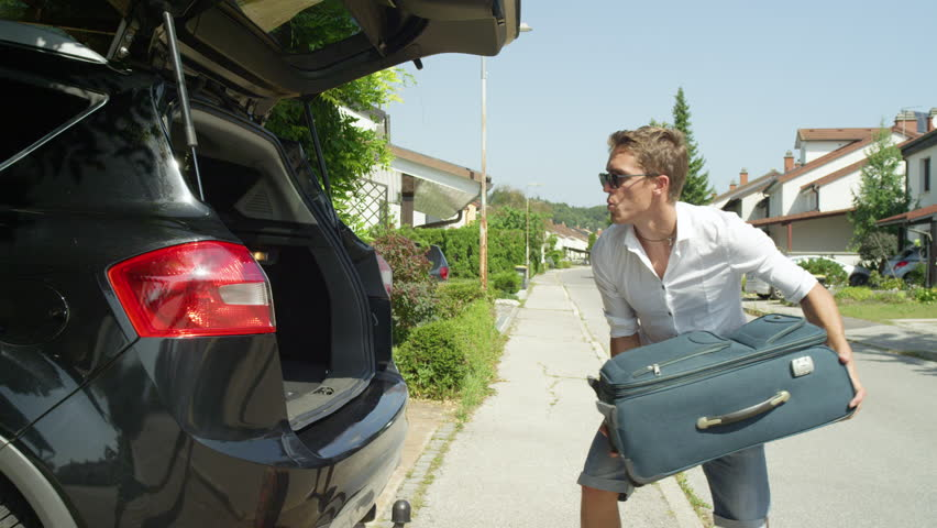 CLOSE UP: Young man is happy to get all the travel bags in the trunk of his car while packing for his awesome journey. Funny shot of carefree guy living in the suburbia tossing luggage in black car.