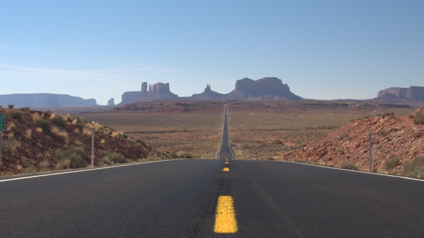 Lonely car driving along an empty straight road leading towards iconic butte and mesa mountains in Monument Valley Utah USA. Travelers traveling into stunning desert Monument valley landmark landscape