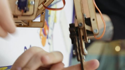 Small toy robot arm helps children to learn and understand robotics technology. Robots and automation are substitute for future human labor. Vertical format video.