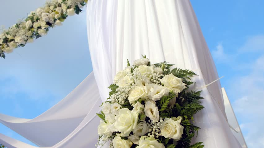 Beautiful video 4k of the Jewish Hupa with conducting of the camera from top to down, wedding putdoor .Beautifully registered Huppa with a set of flowers.Closeup on a bouquet from roses.