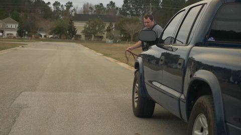 A police uses a K9 dog to inspect a truck to check for possible drugs or explosives.