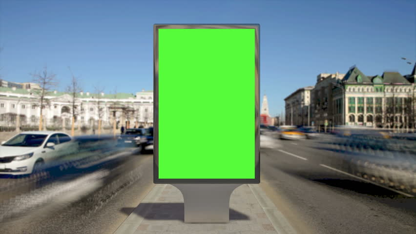 Street billboard stand with green screen on safety island with time lapse traffic. Seamless loop.