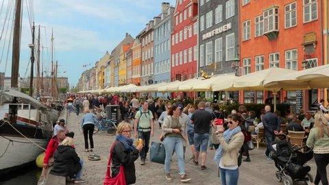 COPENHAGEN, DENMARK - MAY 10, 2018: Nyhavn touristic harbor in Copenhagen with many people passing by