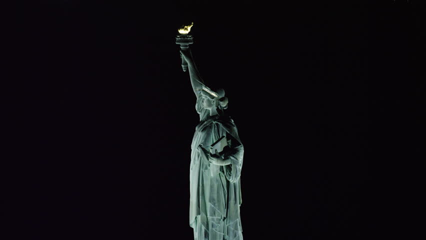 Aerial view of Statue of Liberty in New York City at night. Shot with a RED camera. 4k footage.