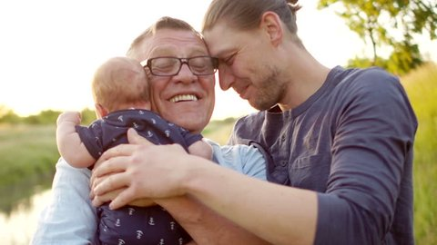A happy young man hugs his father and newborn son. Father's love. the continuity of generations. Male tenderness. Fathers Day