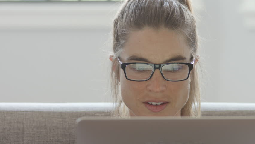 An attractive woman working on her computer on a couch, 4K slow motion | Shutterstock HD Video #1011898844