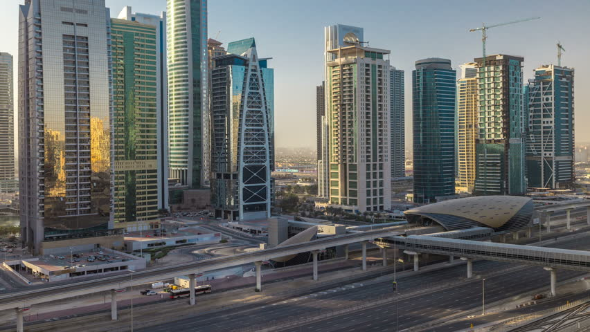 Aerial view of Jumeirah lakes towers skyscrapers during sunrise timelapse with traffic on sheikh zayed road and metro line. Rooftop view from Dubai marina with morning light