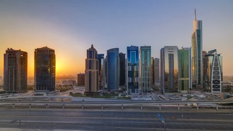Aerial view of Jumeirah lakes towers skyscrapers at sunrise timelapse with traffic on sheikh zayed road and metro line. Rooftop view from Dubai marina