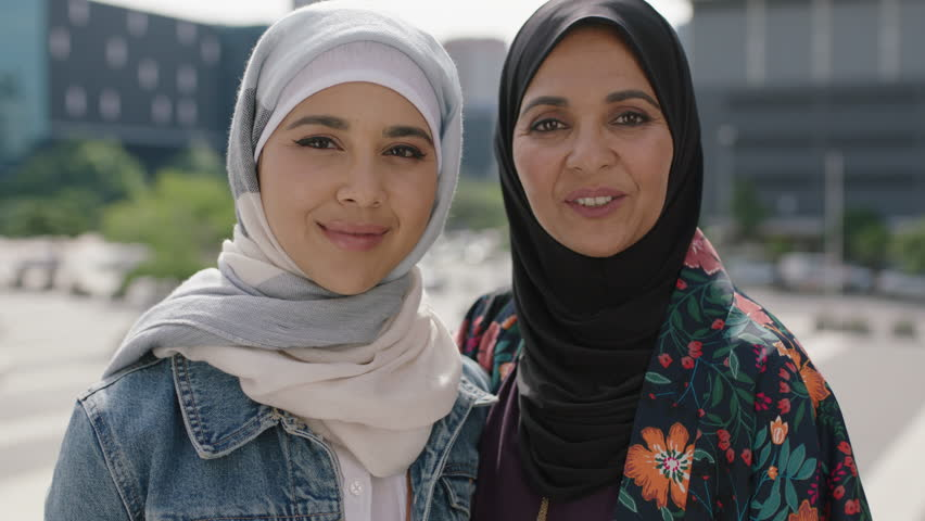 Close up portrait of happy mother and daughter smiling cheerful pose in urban city wearing traditional muslim hijab headscarf  | Shutterstock HD Video #1011926174