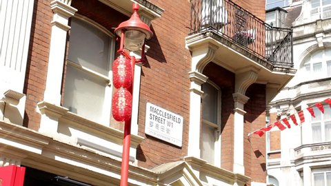 London, England – May 2018: Chinese Lanterns and flags in the breeze by street sign of Macclesfield Street in London's Chinatown.