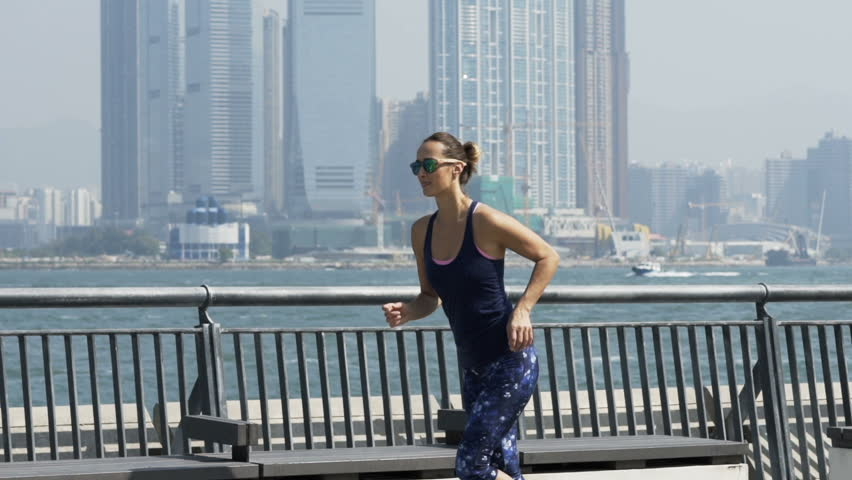 Young, sporty woman jogging in city by river, super slow motion  #1011932144