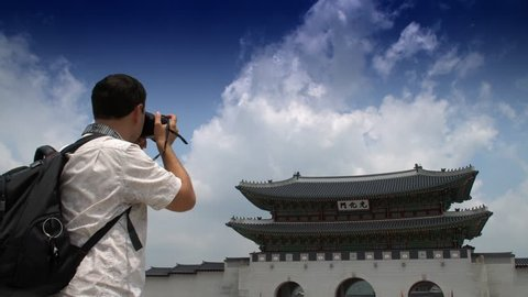 Young Male Traveler Taking Photo of Gwanghwamun Gate in Gyeongbokgung Palace, with the name of the palace 'Gyeongbokgung' on a sign