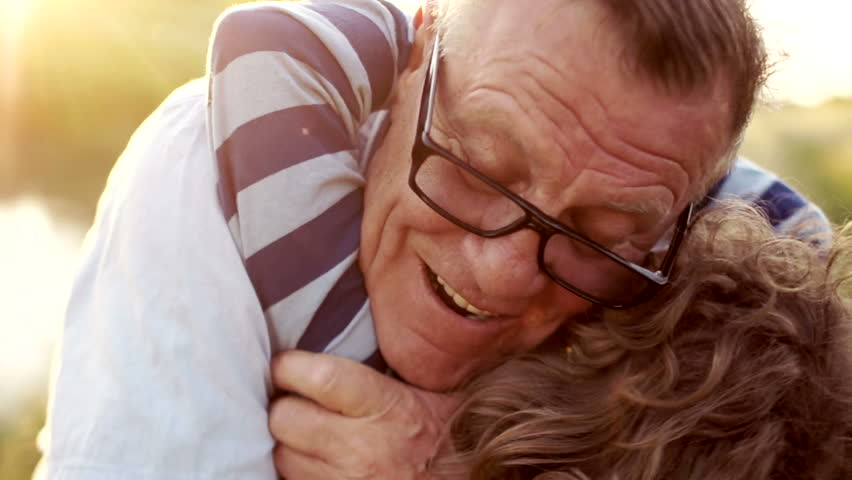 Closeup portrait of a mature man hugging his late son. Happy fatherhood. Curly child, a man wearing optical glasses. Colorful sunset | Shutterstock HD Video #1011945614