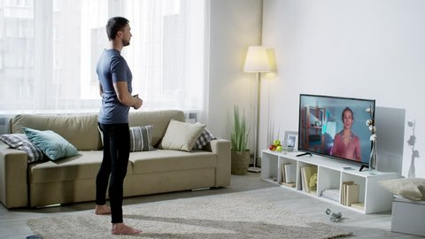 Wide shot of man in sportswear looking at online personal trainer on TV screen and doing boxer squat punch exercise at home