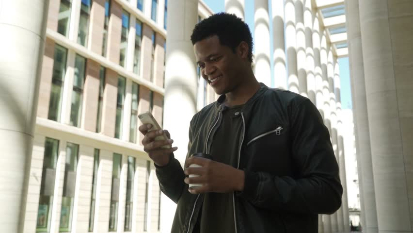 Medium shot of young African American man in black leather jacket holding disposable coffee cup, using mobile app to send and receive text messages and laughing | Shutterstock HD Video #1011950984