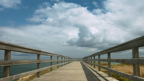 Horizon sky and sea stunning timelapse over an empty pier on the cliff