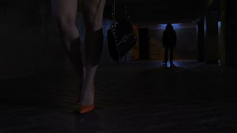 Female slim legs in high heels and mini skirt walking on the foreground in dark underpass subway at night. Male silhouette walking on the background chasing and following lonely female