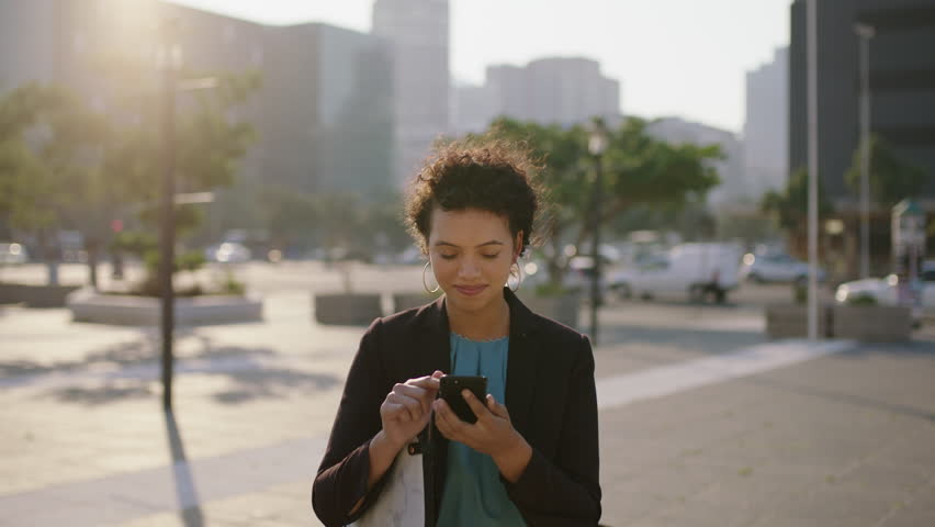 Portrait of young hispanic business woman intern smiling enjoying texting browsing using smartphone social media app in city at sunset commuting lifestyle