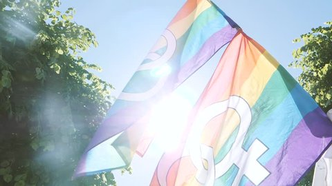Sunlight flare over lesbian and gay gender symbols on two gay rainbow flag in slow motion at Lesbian Gay Bisexual Transgender LGBT GLBT visibility march pride - waving in slow motion