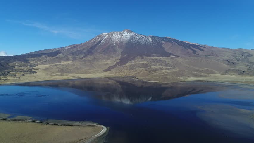 Tromen volcano in national park, Patagonia. Aerial scene moving backwards. Mountain with bed of lava and snow. Tromen lagoon with refletion of volcano. Wilde lonely landscape