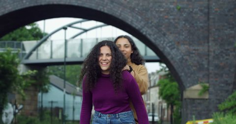 Beautiful Young Mixed Race Twin teen Girls playing piggy back and having fun. Two Multi-Racial Curly hair Teenagers friends with Inner City bridge and British town housing. Sisters playing together.