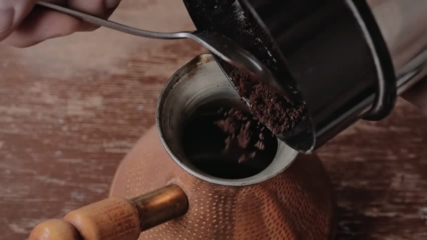 Slow Motion: Putting coffee into traditional turkish copper coffee pot (cezve)
