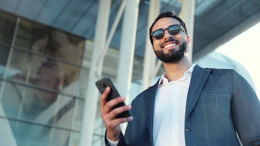 Portrait of Multinational Businessman using Mobile Phone for Social Network. Business Building on the Background. Classical Suit Dressed on.  #1012045064