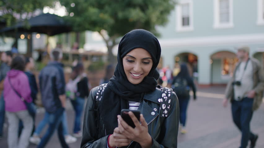 portrait of young beautiful muslim woman using smartphone browsing social media looking puzzled confused wearing headscarf