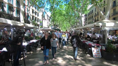 Barcelona, Spain - May 14, 2018: Stabilized walking footage along La Rambla famous street with crowds of locals and tourists, on a sunny day