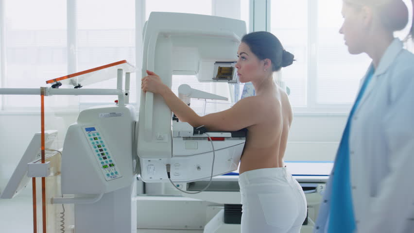 In the Hospital, Side View Shot of Topless Female Patient Undergoing Mammogram Screening Procedure. Healthy Young Female Does Cancer Preventive Mammography Scan. Shot on RED EPIC-W 8K Camera.