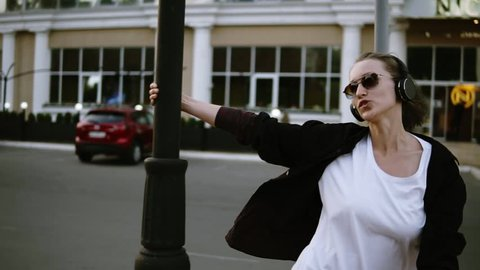 A beautiful girl with sunglasses and headphones dancing, circling around a lamppost. Laughing. Happy lifestyle